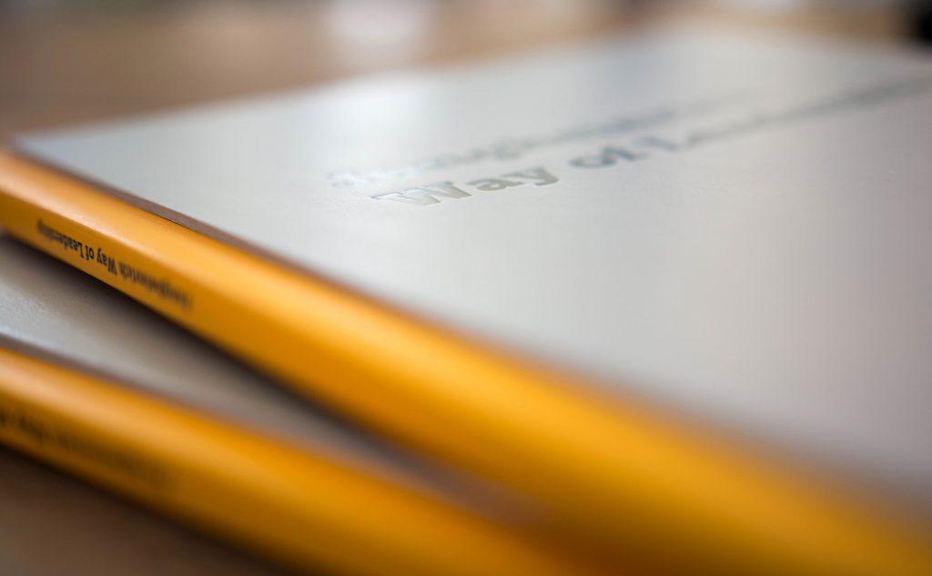 Vollflächige Verklebung von einem Hardcover mit einer Fadenheftung für hochwertige Broschüren und Bücher.