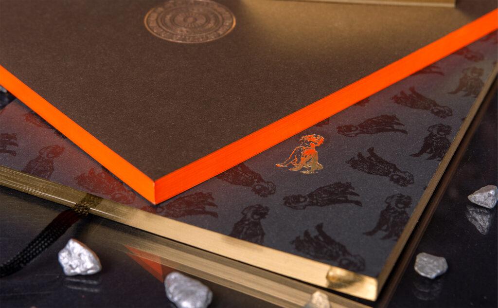 Eindrucksvolles Design von einem Notizheft mit einer Heißfolienprägung in Kupfer und einem Farbschnitt in Neonorange.